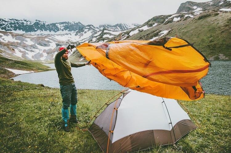 Plandid na Instagram - mężczyzna rozkłada namiot w górach