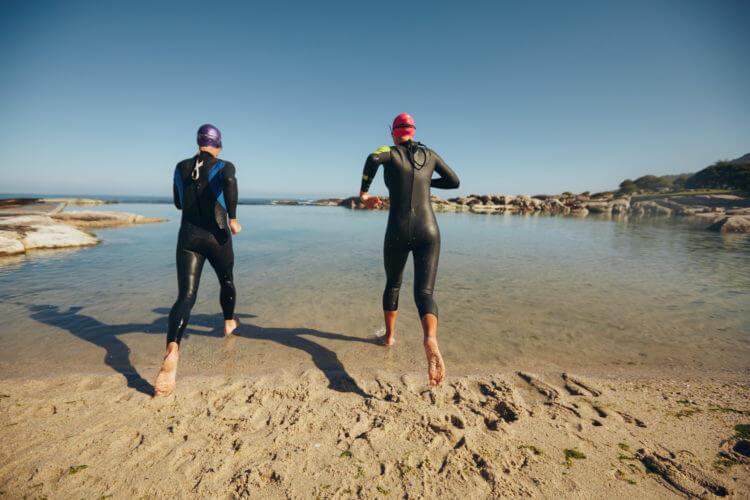 triatlon zawodnicy wbiegają do wody