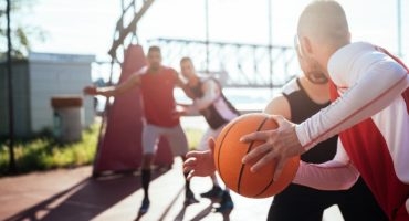 chłopaki grają na boisku w koszykówkę