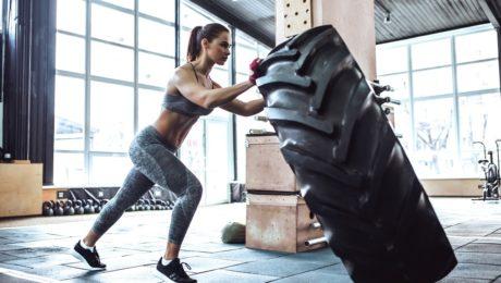 Dziewczyna na siłownia ćwiczenia z oponą