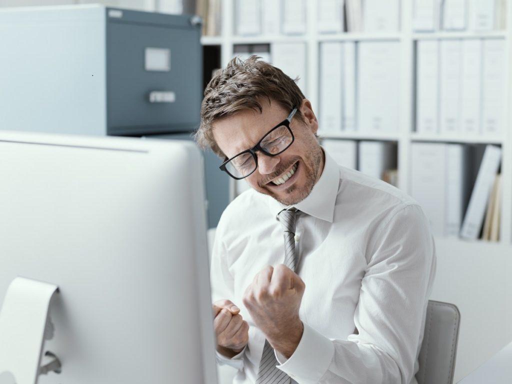 Szczęśliwy specjalista siedzi przy biurku